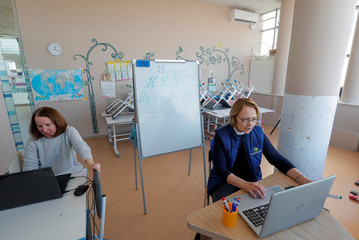 Teachers conduct a lesson online using a computer in a private school amid coronavirus disease (COVID-19) outbreak in Minsk