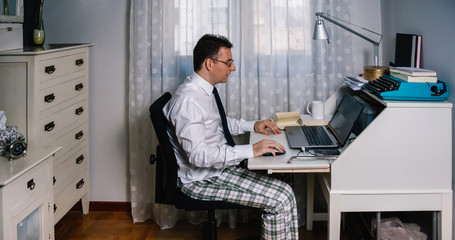 Man working from home with laptop wearing shirt, tie and pajama pants Wall mural