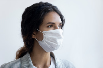Hopeful young woman wear medical face mask protecting from coronavirus look in distance think of...