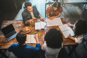 Group of friends studying on the kitchen table in an apartment - Millennials help each other with books and notes - Team of teamwork - Top view
