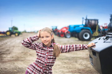 Wall Mural - Cute girl near the modern tractor in the field.