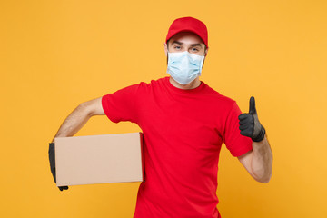 Delivery man employee in red cap blank t-shirt uniform face mask glove hold empty cardboard box isolated on yellow background studio Service quarantine pandemic coronavirus flu virus 2019-ncov concept