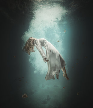 Caucasian woman with long white dress floats underwater
