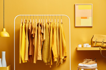 Vivid yellow wardrobe with clothes on rack