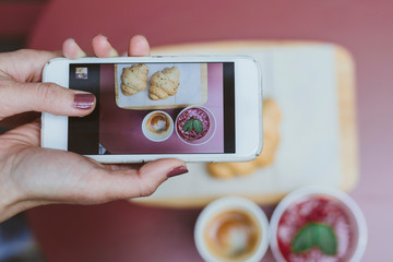 Woman taking photos of her breakfast