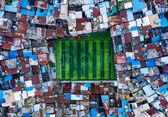 Aerial view of football field amidst residential buildings in city