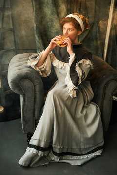 Young woman eating burger while sitting on armchair