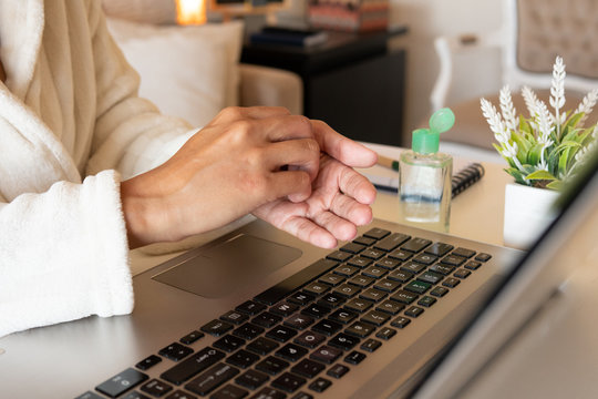 Hands of Adult african american woman cleaning hands with sanitizer gel in front of laptop at home. Sleeves of robe. Working from home due Coronavirus or Covid-19 quarantine.