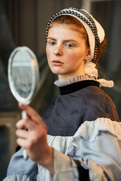 Portrait of young woman looking into mirror
