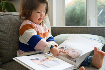 Little girl looking at baby book