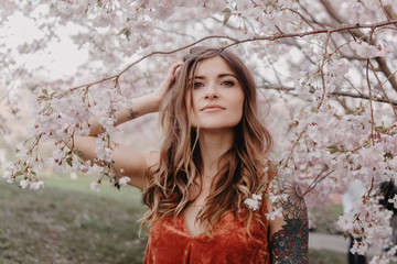 A young blonde woman standing amongst the cherry blossom trees