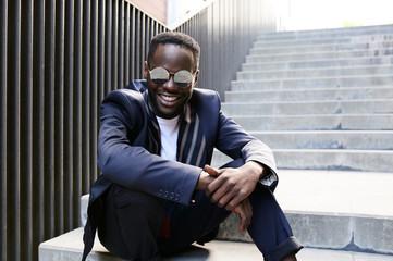 Elegant black afro businessman smiling.