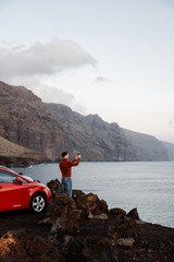 Man taking photo on smartphone of sea waves.