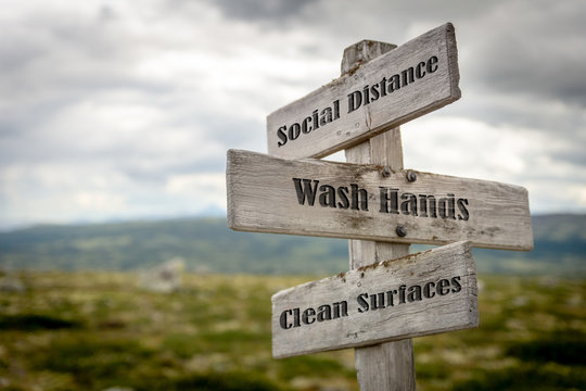 Signpost outdoors with the text social distance, wash hands and clean surfaces to illustrate three basic rules for people to follow during the global pandemic of coronavirus or Covid-19 epidemic.