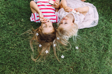 Two little girls lying on the grass