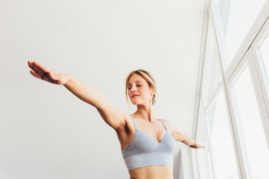 Beautiful young woman doing yoga postures in luxury apartment