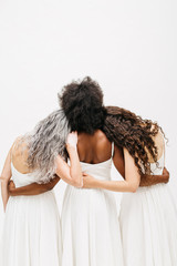 Rear view of women embracing each other