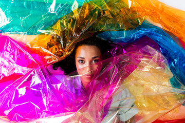 Portrait of young woman with multicolored plastic