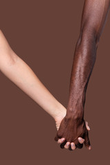 Crop view of white woman and black man holding hands