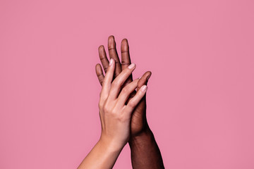 Hands of white woman and black man touching