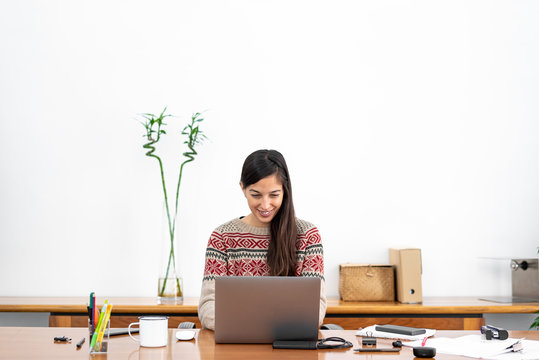 Young freelancer working from a makeshift home office connected to the internet with a laptop and a phone during the period of global confinement