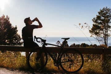 Anonymous Road Cyclist Taking Break and Drinking
