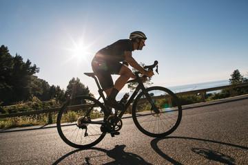 Caucasian Man on Road Bike Racing Uphill Fototapete