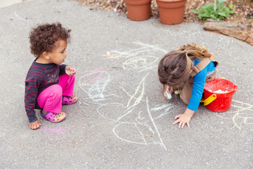 Pair of cute kids playing and drawing on an asphalt driveway with large pieces of chalk