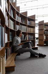 Student with book at bookcase in library