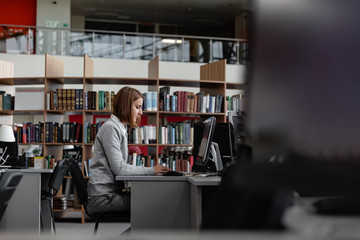 Woman working on computer in library