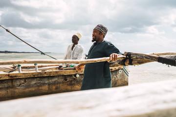 the arrival of two fishermen after a fishing day in Zanzibar, Tanzania
