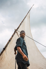 Portrait of a fisherman in his sailing boat. He is looking at th