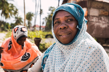 coexistence of two zanzibari women. One is smiling and the other is in the background