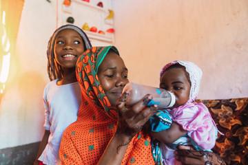 Zanzibari mother feeding the baby with the baby bottle