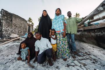 Portrait- Muslim zanzibari family, adults and children posing on the white sand.