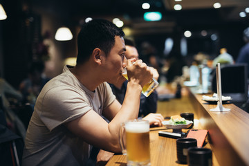 Portrait of man drinking beer in pub