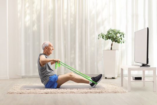 Senior man exercising with an elastic band in front of a tv at home