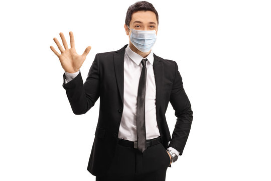 Young man in a suit wearing a medical protective mask and showing clean hands