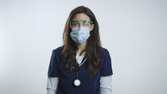 Nurse wears protective goggles and mask as she looks to camera
