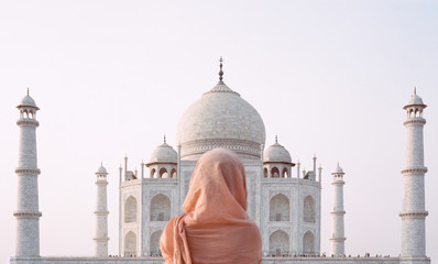 Young woman in traditional indian clothes in front of Taj Mahal in Agra, India
