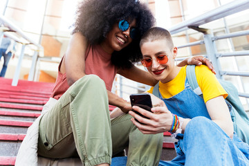 Portrait of young women taking selfie while sitting on steps