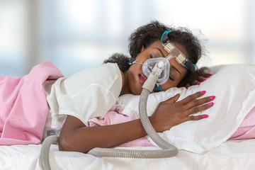 Woman wearing CPAP headgear to sleep against apnea