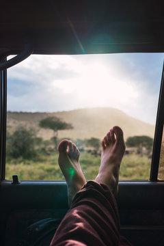 Nice crossed male feet in the car window. Close up of feet, Sunrise in the savannah.