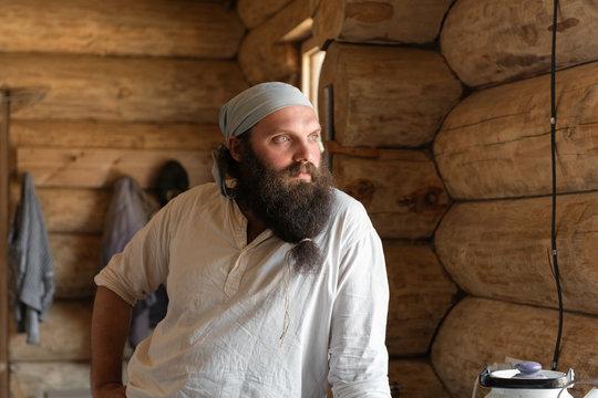 Bearded artisan in log house