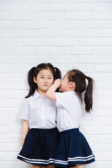 One of cute schoolgirl whispering to another