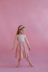 Lovely little girl in pink dress dancing by pink background