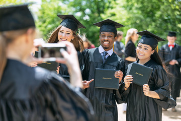Young woman taking picture of friends with diploma after graduation ceremony on campus