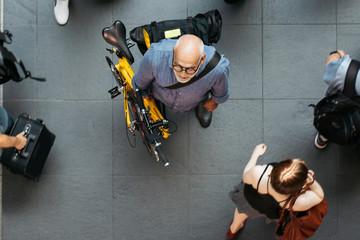 Older Man With Folding Bike Waiting in Public