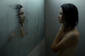 Woman in shower looking at mirror