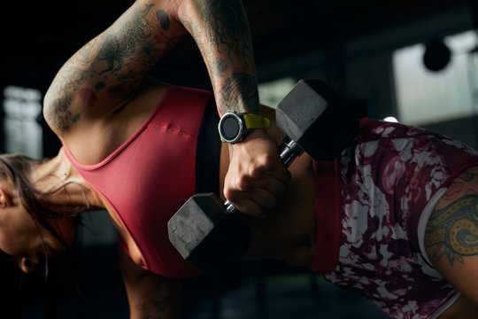 Athlete woman practicing with dumbbells.